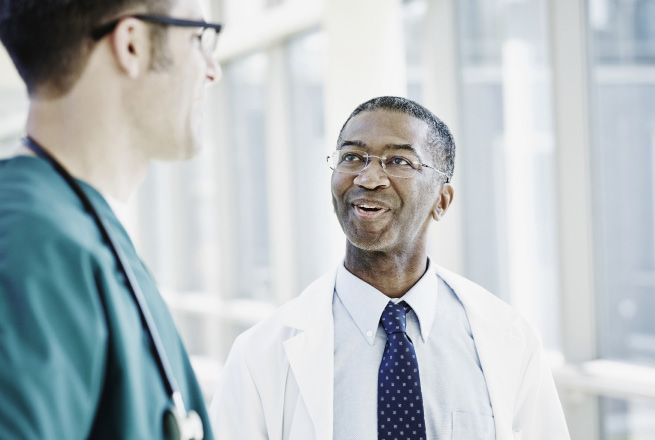 Physicians holding a conversation in the hallway.
